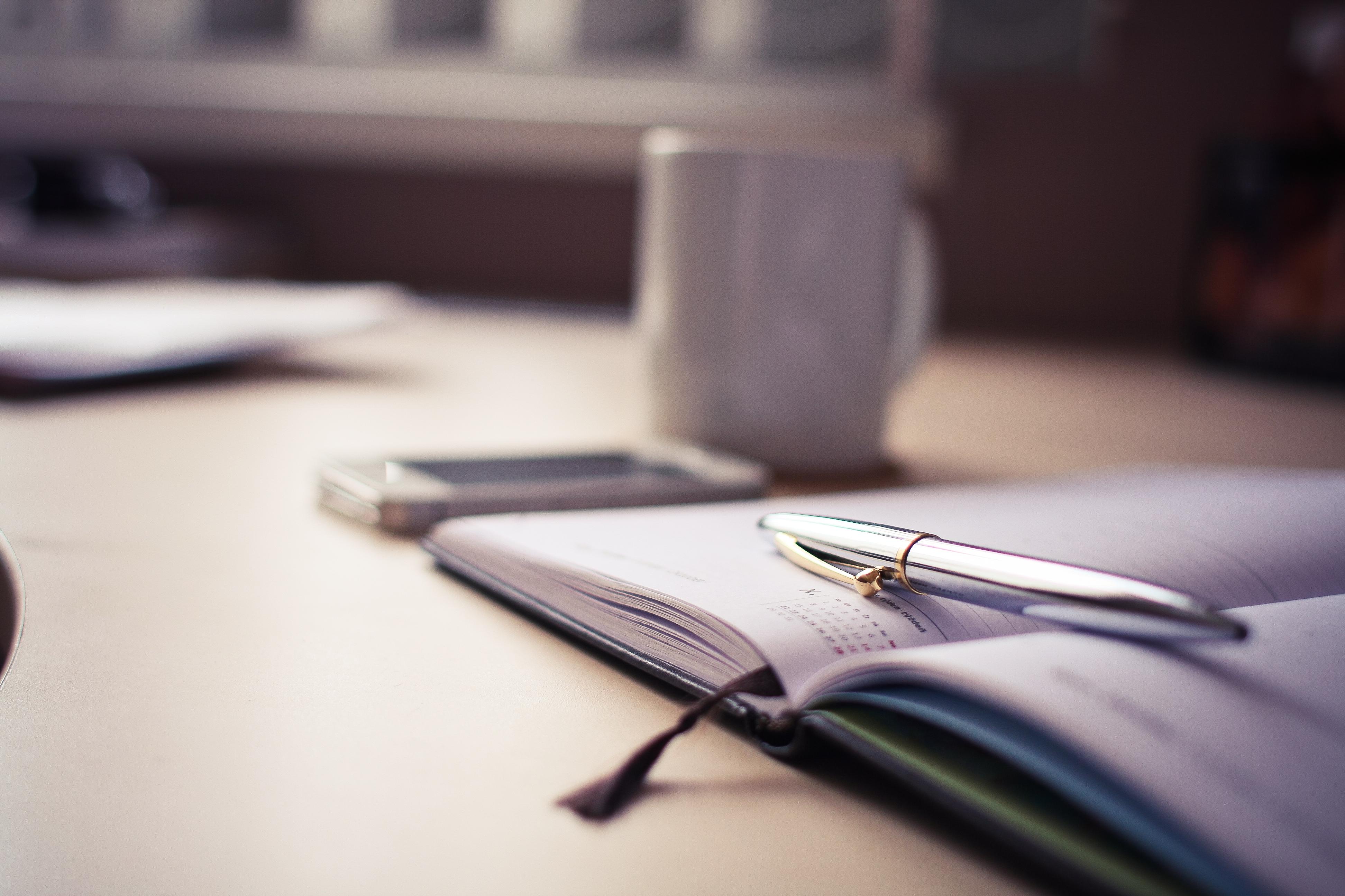 Silbernern Stift, Block Und Kaffeetasse Auf Schreibtisch Als Symbol Für Kosteneinsparung Durch Innovative Lösungen