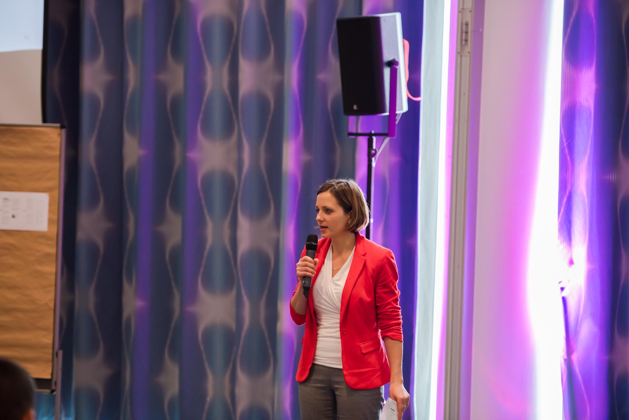 Nina Defounga im roten Jacket spricht auf der Bühne der Innovationskonferenz TFC2015