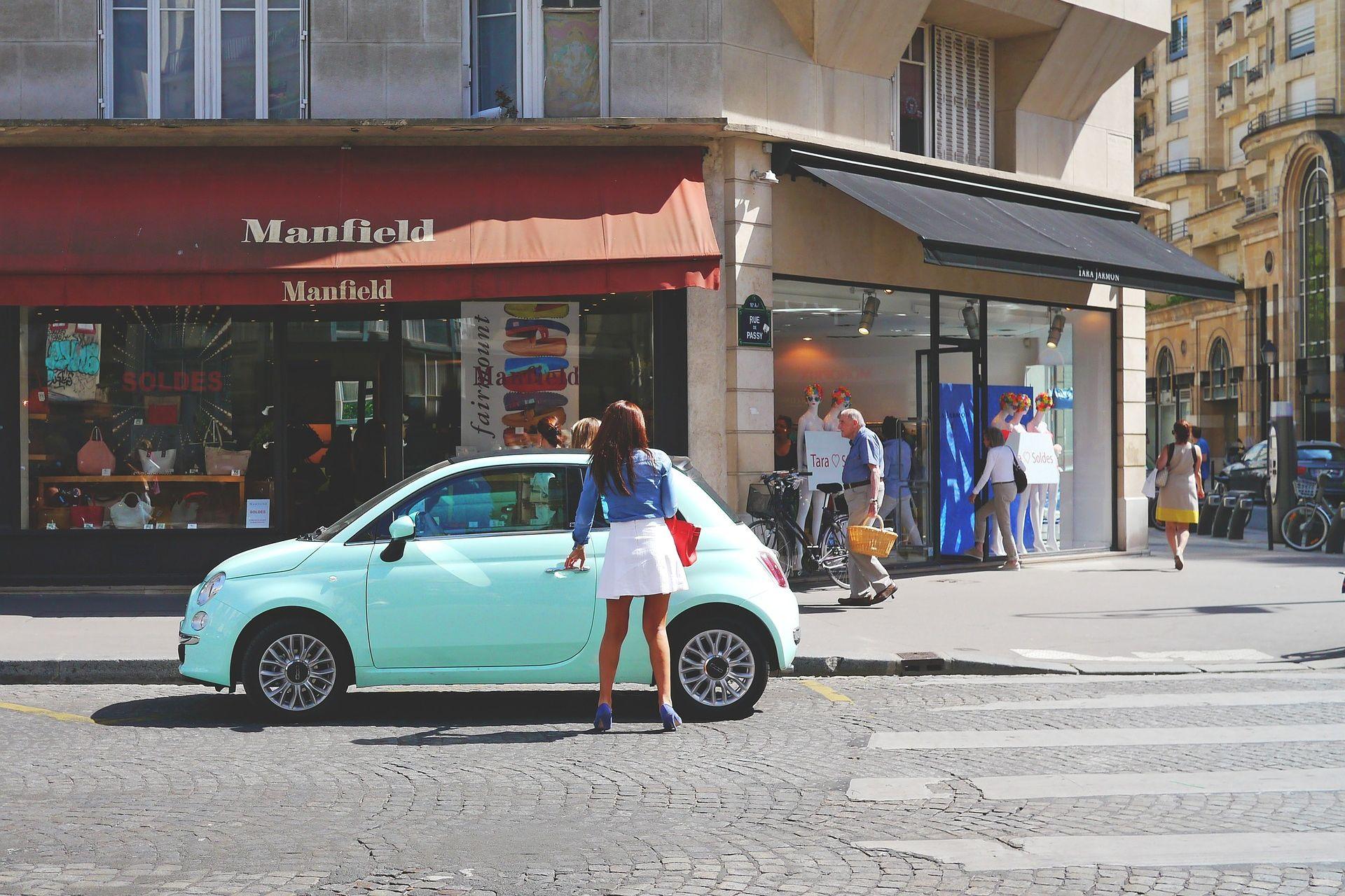 Frau steigt an der Hauptstraße in ein türkisfarbenes, privates Carsharing-Auto ein als Beispiel für eine Geschäftsmodell-Innovation der Innovationsarten