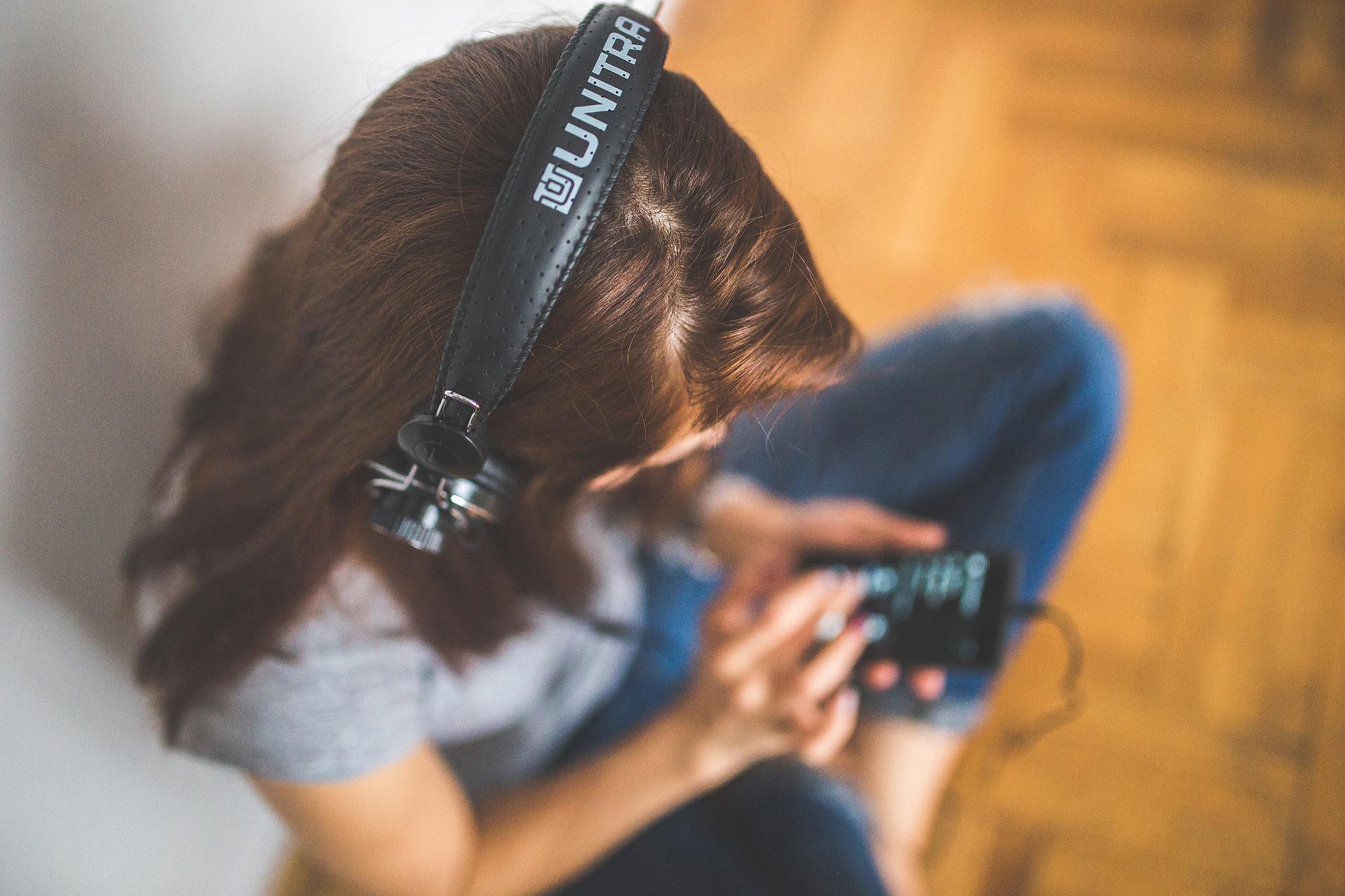 Frau hört Musik mit Kopfhöhrern und bedient Ihren mp3-Player als Beispiel für eine Geschäftsmodell-Innovation der Innovationsarten