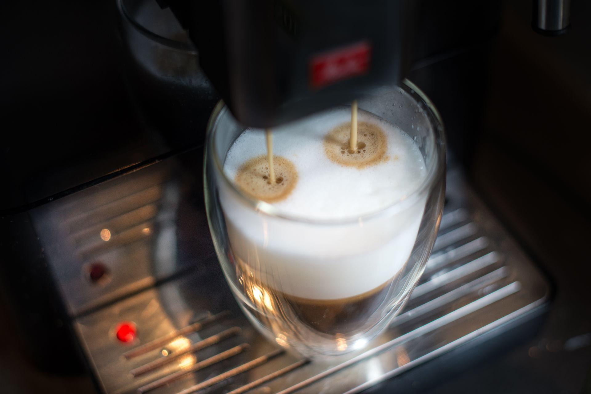 Espresso läuft aus einem Kaffeevollautomaten in ein Glas mit Milchschaum als Beispiel für eine Produkt-Innovation der Innovationsarten