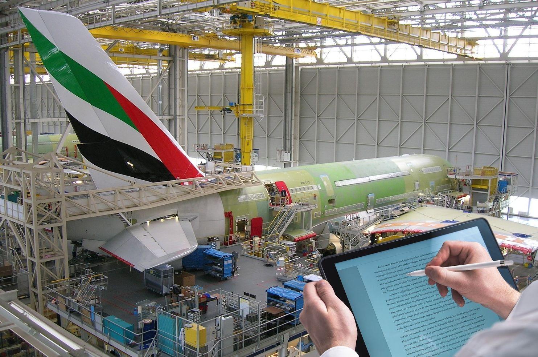 Hand mit Stift schreibt auf einem Tablet vor Flugzeugfertigung im Hangar als Beispiel für eine Prozess-Innovation der Innovationsarten