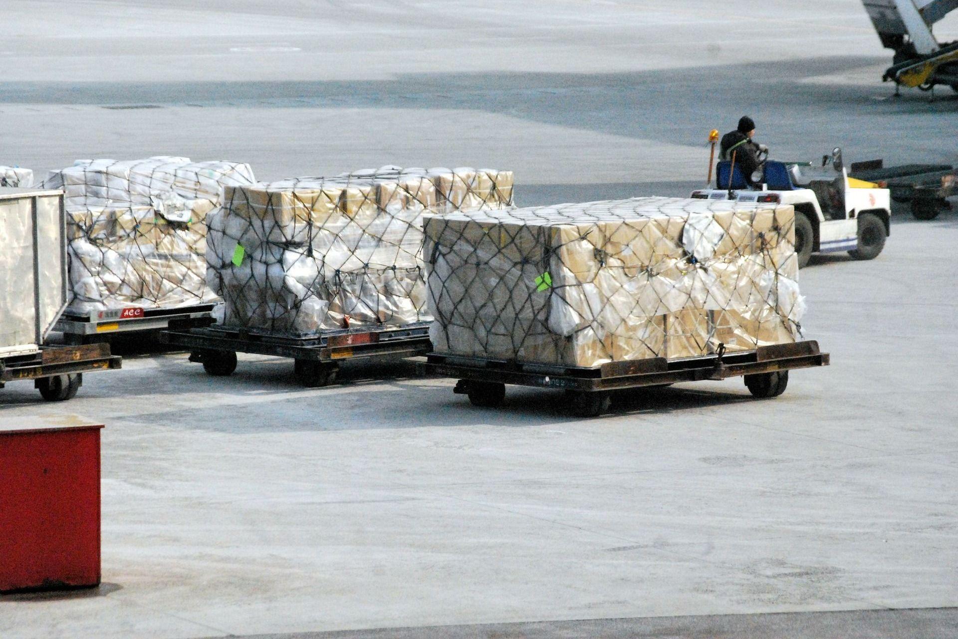 Logistische Gepäckanhänger auf dem Rollfeld als Beispiel für eine Service-Innovation der Innovationsarten