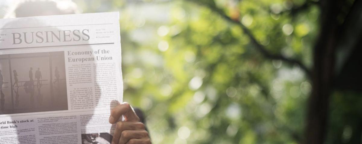 Mann im Sonnenlicht hinter einer aufgeschlagenen Zeitung