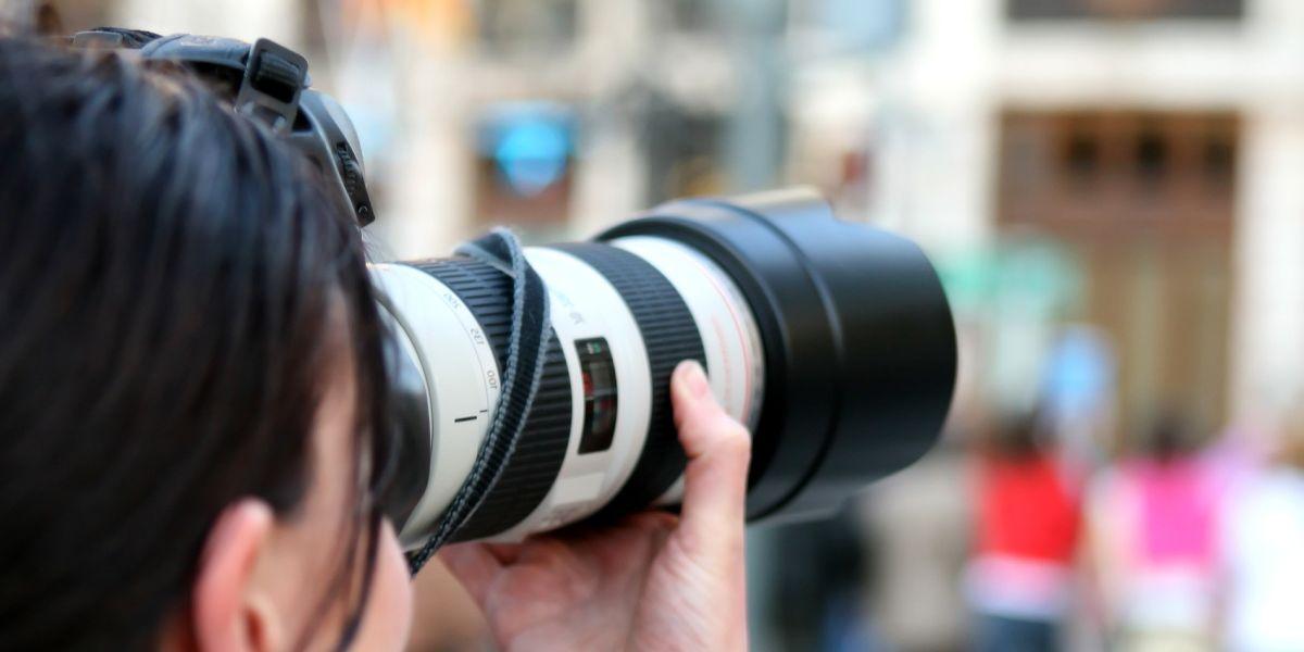 Fotografin mit Teleobjektiv fokussiert auf etwas außerhalb des Bildausschnittes