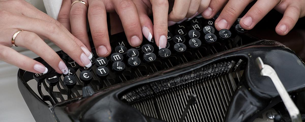 Viele Hände tippen auf einer alten Schreibmaschine