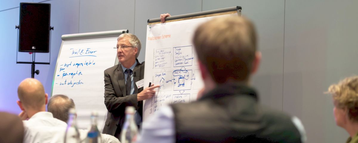 Innovationsberater diskutiert mit Managern an Flipchart-Skizze