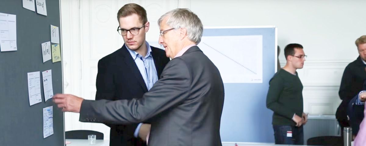 Coach und Coachee diskutieren an der Metaplanwand