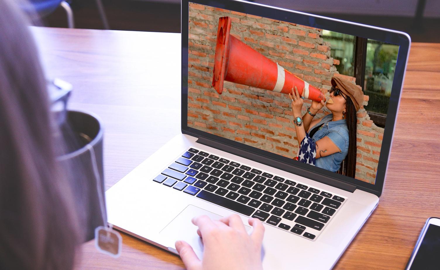 Frau mit Sprachrohr auf Laptopbildschrim als Symbol für Webinar Innovationskommunikation - TOM SPIKE