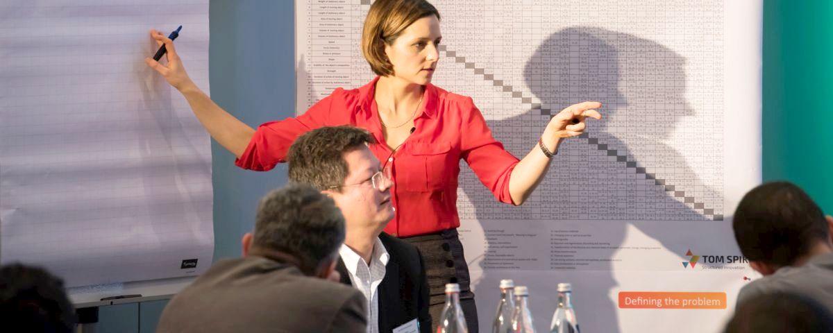 Innovationstrainerin mit roter Bluse vor Flipchart und Publikum