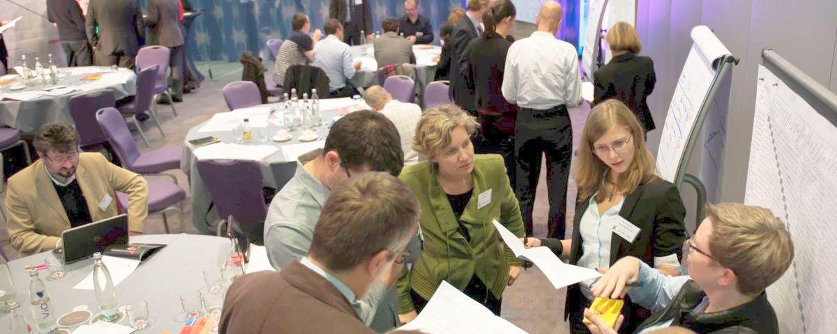 Workshopteilnehmer arbeiten in Gruppen und diskutieren vor Flipcharts