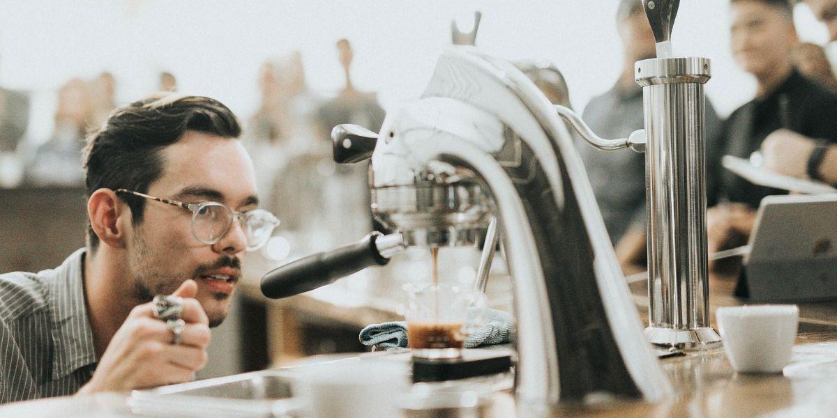 Barrista mit prüfendem Blick an einer glänzenden Kaffeemaschine