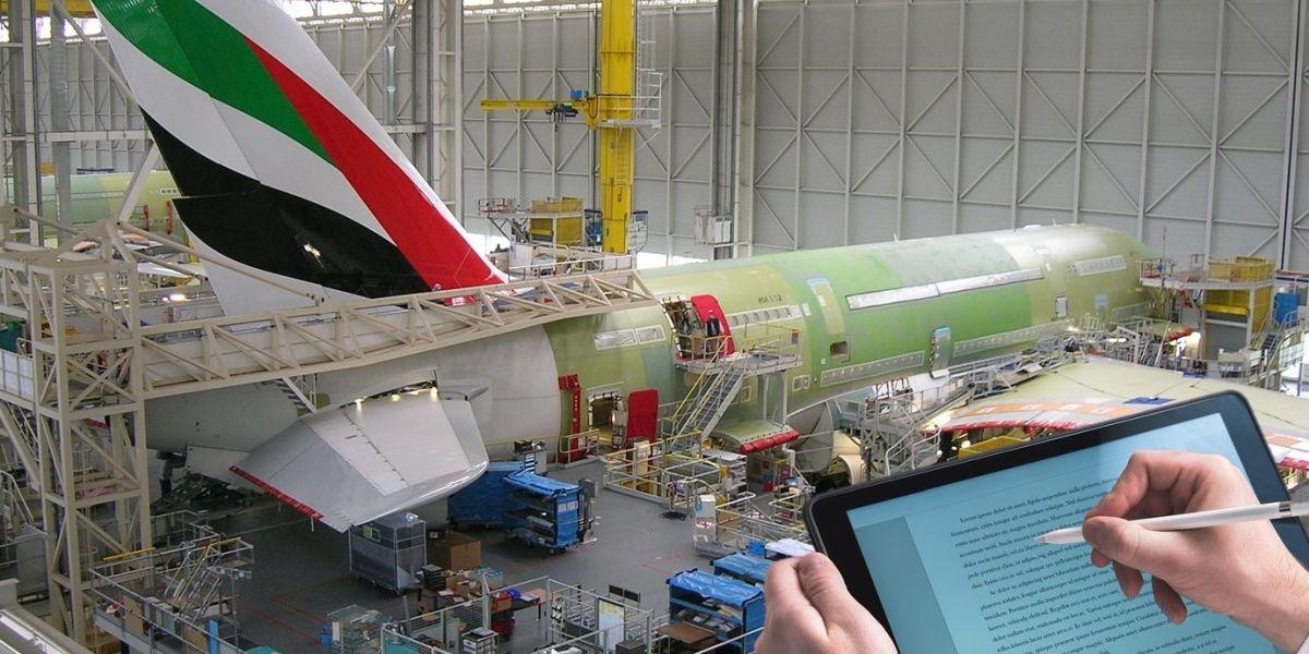 Hände notieren Informationen auf einem Tablet vor der Montage und Lackierung eines Passagierflugzeugs