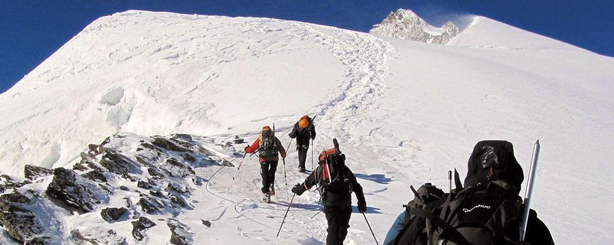 Vier Bergsteiger in Ausrüstung wandern auf Schnee in Richtung Berggipfel