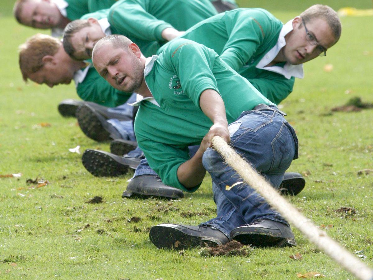 Männer in grünen Hemden beim Tauziehen in eine gemeinsame Richtung