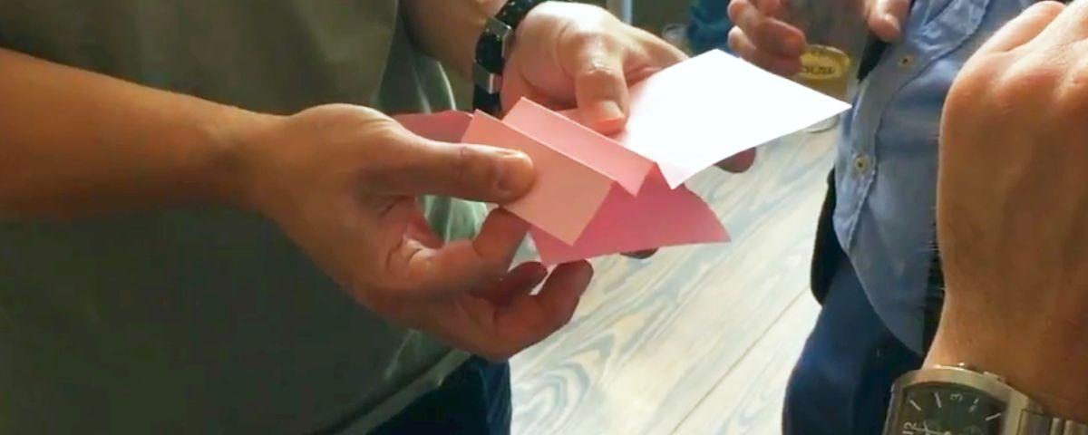 mehrere Hände arbeiten an gefaltetem Papier
