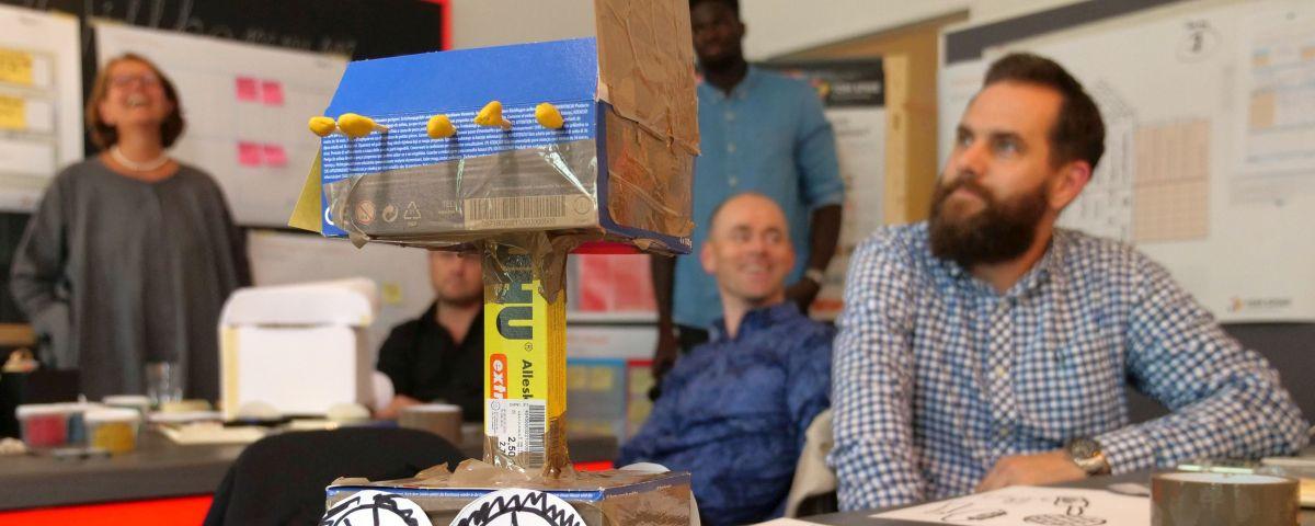 Design Thinking Workshopteilnehmer mit Prototyp aus Papier und Pappe