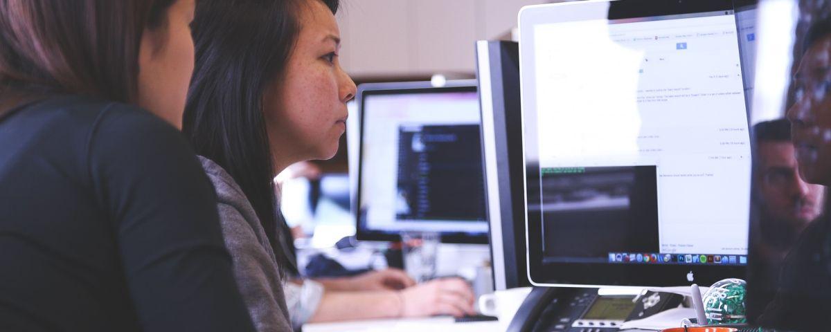 Zwei Frauen arbeiten gemeinsam am Bildschirm als Symbol für innovatives IT-System - TOM SPIKE