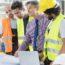 Manager Und Fachkräfte In Der Industriehalle Als Symbol Für Gemeinsame Innovation - TOM SPIKE