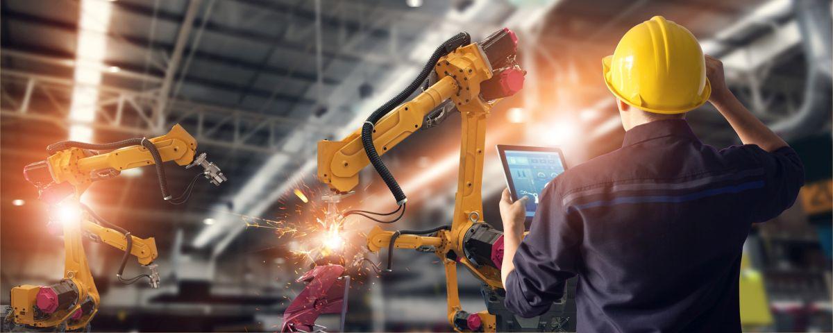 Schweißroboter Und Mitarbeiter Mit Helm Und Tablet Als Symbol Für Geschäftsmodellinnovation In Industrieunternehmen - TOM SPIKE