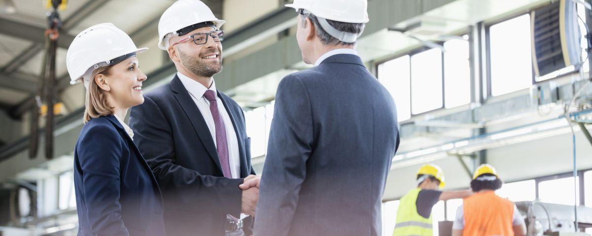 Führungskräfte schütteln Hände in Industriehalle zum Innovationerfolg - TOM SPIKE