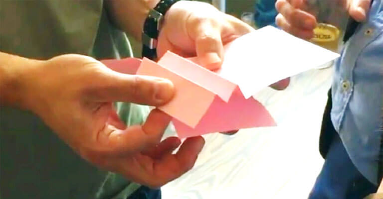 Hands folding pink paper in a workshop as a symbol for creative invention workshop Patent Booster - TOM SPIKE