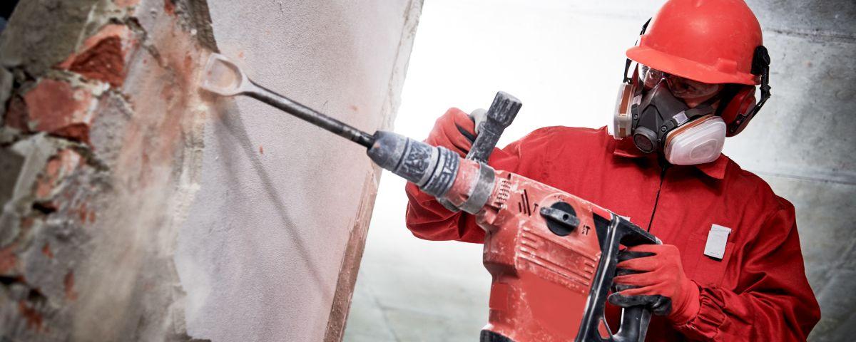 Bauarbeiter mit Helm und Bohrhammer als Symbol für Geschäftsmodellinnovation in der Bauindustrie