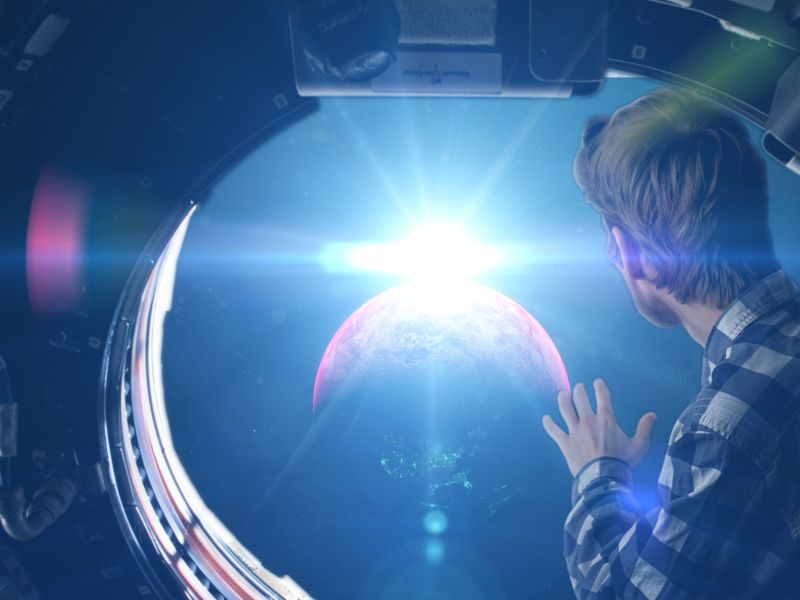 Young man looking out of space ship window seeing Earth as a symbol for Product Innovation - TOM SPIKE