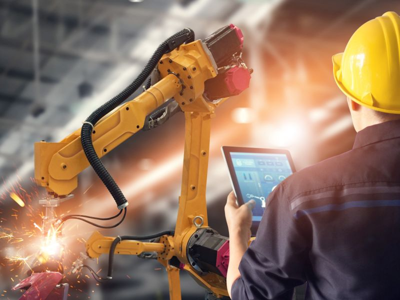 Technician controls robot with tablet as a symbol for business model innovation - TOM SPIKE