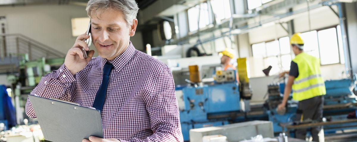 Manager Telefoniert Zur Produktidee Mit Klemmbrett Und Fabrik Im Hintergrund - TOM SPIKE