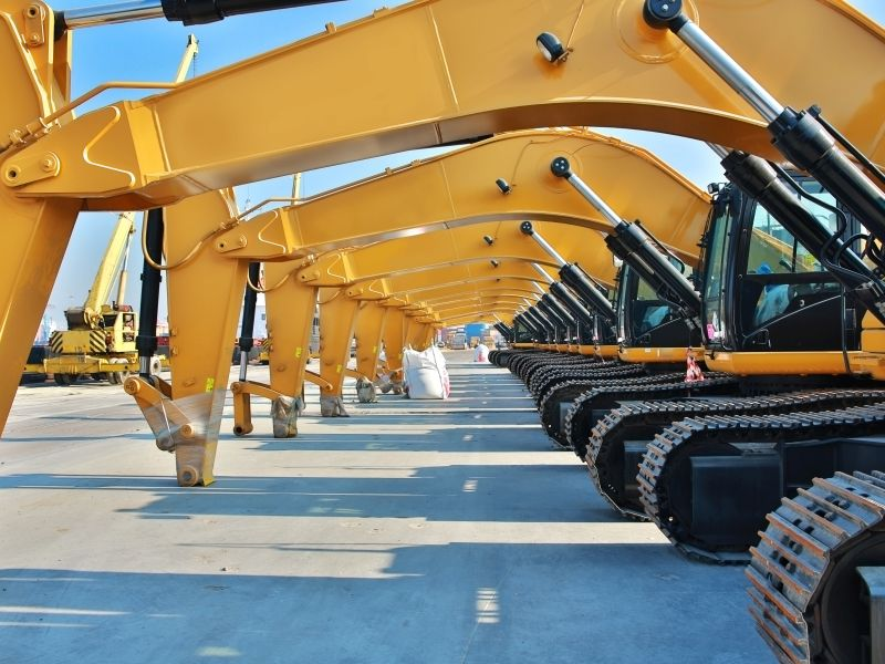 Parked yellow excavator as a symbol for utilization management in construction - TOM SPIKE