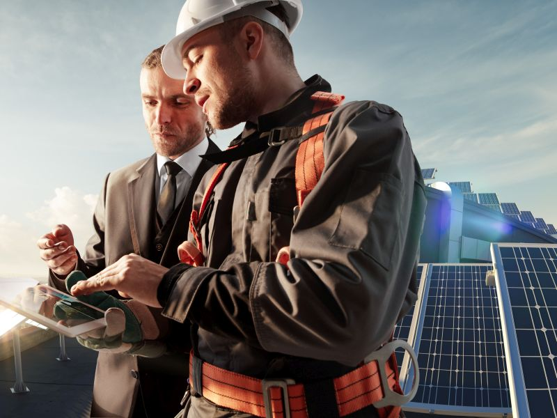 Technicians and managers on the solar roof with tablet as a symbol for digital service accounting - TOM SPIKE