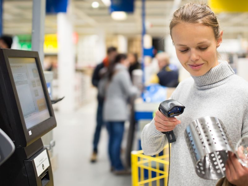 Buyer scans the product at the self-service checkout as a symbol of service innovation - TOM SPIKE