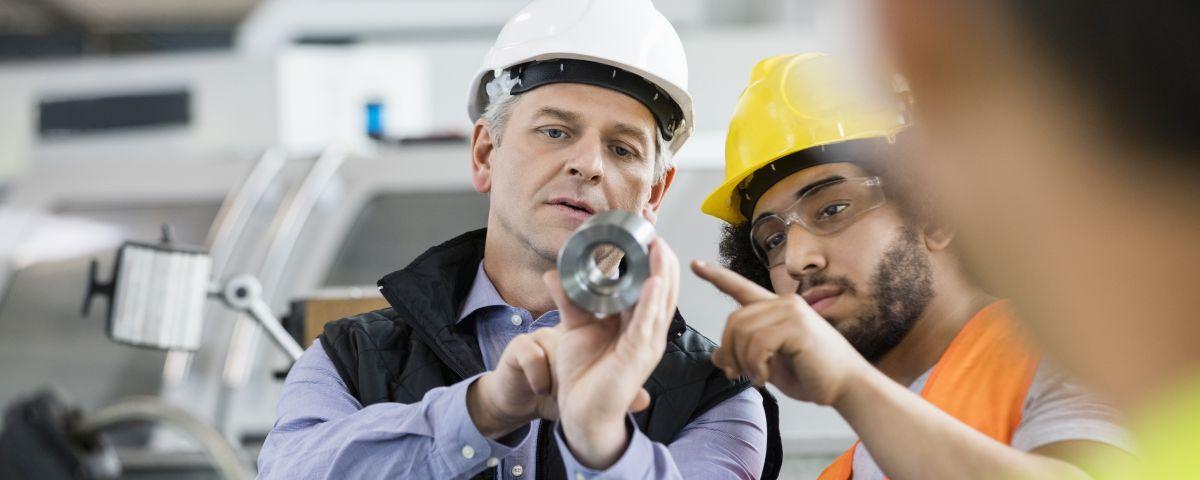 Entwicklungsleiter und Ingenieur untersuchen Bauteil als Sinnbild für Technologieinnovation - TOM SPIKE