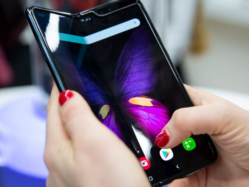 OLED Smartphone in woman's hands as a symbol for Technology Innovation - TOM SPIKE